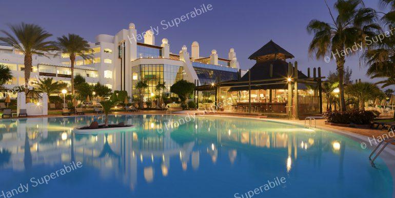 Vista exterior nocturna de la piscina